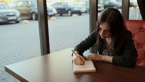 Teenage student makes sketches in notebook in cafe stock footage