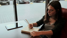 Teenage student makes sketches in notebook in cafe stock video footage