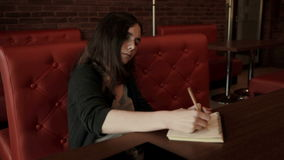 Teenage student makes sketches in notebook in cafe stock video