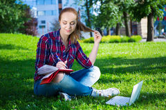 Teenage student or school girl sitting in park Royalty Free Stock Photo