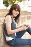 Teenage Student Sitting Outside Using Mobile  Stock Photos