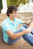 Teenage Student Sitting Outside Using Mobile Phone. Male Teenage Student Sitting Outside On College Steps Using Mobile Phone Royalty Free Stock Images
