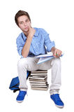 Teenage student sitting on a stack of his textbooks. On white background stock photos