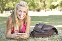 Teenage Student Texting In Park Stock Photos