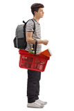 Teenage student waiting in line with a shopping basket. Full length profile shot of a teenage student waiting in line with a shopping basket isolated on white Royalty Free Stock Images