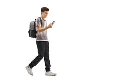 Teenage student walking and looking at a phone. Full length profile shot of a teenage student walking and looking at a phone isolated on white background Royalty Free Stock Photography