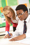 Teenage Student Working In Classroom. With Teacher Stock Photos