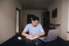 A teenage student writes a task in a notebook sitting at a table near the computer. Student studies at home. A teenage student writes a task in a notebook Royalty Free Stock Images
