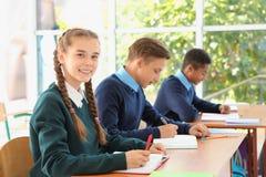 Teenage students in classroom. Stylish school uniform stock photos