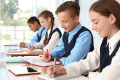 Teenage students in classroom. Stylish school uniform royalty free stock image