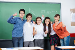 Teenage Students Gesturing Thumbs Up Together. Group of teenage students gesturing thumbs up together in classroom Stock Photo