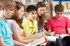 Teenage Students In Library Reading Books. Smiling Royalty Free Stock Photos