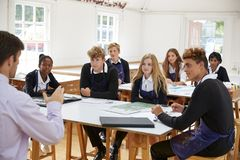 Teenage Students Listening To Teacher In Art Class royalty free stock photo