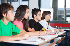 Teenage Students Looking Away While Studying At Stock Photo