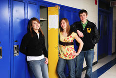 Teenage Students at School Lockers. Three teenage students loiter around high school lockers in hallway royalty free stock photography
