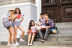 Teenage students sitting on stone steps in front of university. Stock Photos