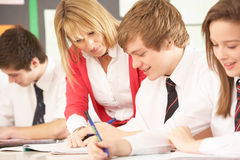 Teenage Students Studying In Classroom. With Teacher Stock Images