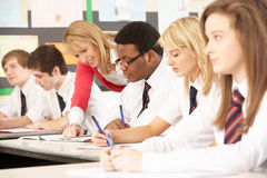 Teenage Students Studying In Classroom. With Teacher Stock Photo