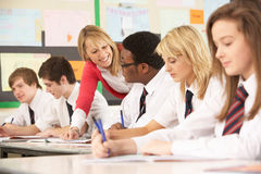 Teenage Students Studying In Classroom. With Teacher Stock Photography