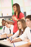 Teenage Students Studying In Classroom. With Teacher Royalty Free Stock Images