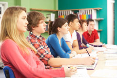 Teenage Students Studying In Classroom Stock Photos