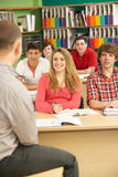 Teenage Students Studying In Classroom With Tutor. With back to camera Royalty Free Stock Photos