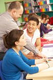 Teenage Students Studying In Classroom With Tutor. Smiling Stock Image