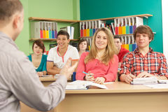 Teenage Students Studying In Classroom With Tutor. Smiling Stock Images