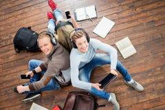 Teenage students studying on the floor Stock Image
