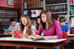 Teenage Students Studying In Library. Male and female teenage students studying in library Stock Photos