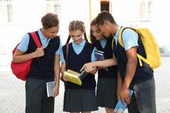 Teenage students in stylish school uniform. Outdoors stock photography