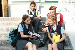 Teenage students in stylish school uniform. On stairs outdoors royalty free stock images