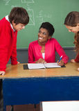Teenage Students With Teacher At Desk In Classroom. High school teenage students with young teacher at desk in classroom Royalty Free Stock Image