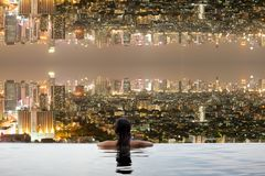 Teenage in swimming pool with city upside down. At night Stock Image