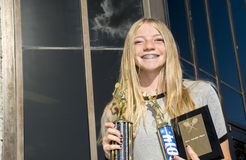 Teenage Tennis Player with Trophies. A Happy Teenage Girls Tennis Player Showing Off Her Trophies Stock Photos