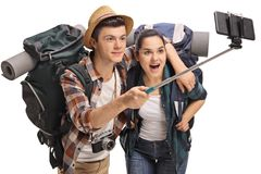 Teenage tourists with backpacks taking a selfie with a stick. Isolated on white background Stock Images
