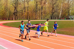 Teenage track sprinters running with British flag. Group of five multiethnic teenage sprinters running with flag of Great Britain on the racetrack Royalty Free Stock Image