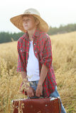 Teenage traveler in farm oat field holding old-fashioned suitcase and looking to horizon Royalty Free Stock Photography