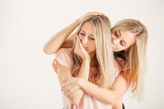 Twins sisters comforting tearful friend on white Stock Image