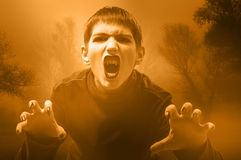 Teenage vampire in the misty forest. Preparing to attack in sepia tones Stock Photo