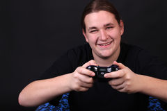 Teenage video game player. Teenager holding a video game controller with happy expression on his face Stock Photography