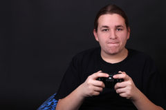 Teenage video game player. Teenager holding a video game controller with intense expression on his face (shallow depth of field Royalty Free Stock Photography