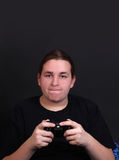 Teenage video game player. Teenager holding a video game controller with intense expression on his face (shallow depth of field Stock Photos