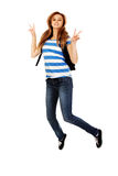 Teenage woman with backpack jumping and gesturing peace Royalty Free Stock Image