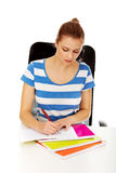 Teenage woman doing homework behind the desk Stock Image