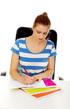 Teenage woman doing homework behind the desk Royalty Free Stock Image