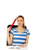 Teenage woman doing homework and holding huge pen Royalty Free Stock Image
