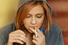 Teenage woman drinking beer and smoking cigarette Stock Photo