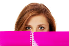 Teenage woman hiding her face behind a notebook Stock Photography