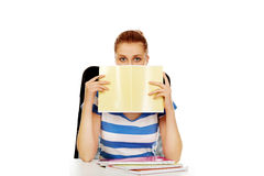 Teenage woman hiding her face behind a notebook Royalty Free Stock Photos